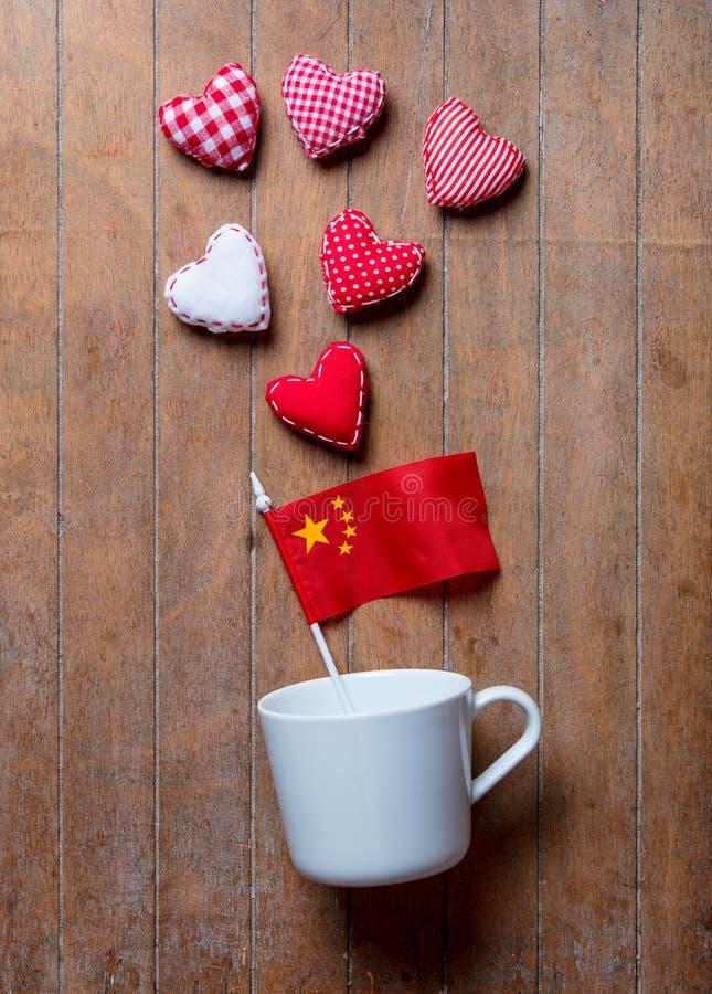Vit kopp på att ligga på sida med Kina flagga- och hjärtaformer fotografering för bildbyråer