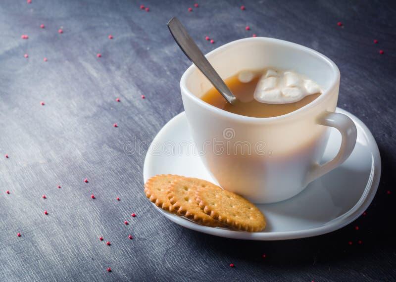 Vit kopp på ett tefat med varm kakao Mörk träbakgrund för morgonfrukost royaltyfri fotografi