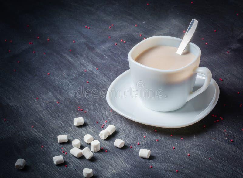 Vit kopp på ett tefat med varm kakao Mörk träbakgrund för morgonfrukost arkivfoton