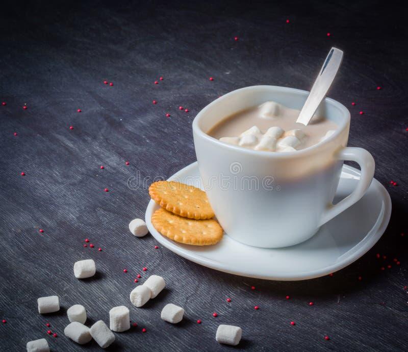 Vit kopp på ett tefat med varm kakao Mörk träbakgrund för morgonfrukost arkivbild