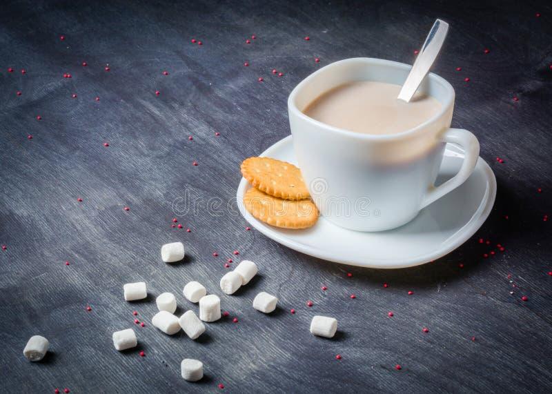 Vit kopp på ett tefat med varm kakao Mörk träbakgrund för morgonfrukost arkivfoto