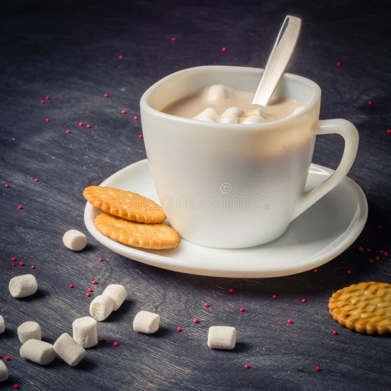 Vit kopp på ett tefat med varm kakao Mörk träbakgrund för morgonfrukost fotografering för bildbyråer