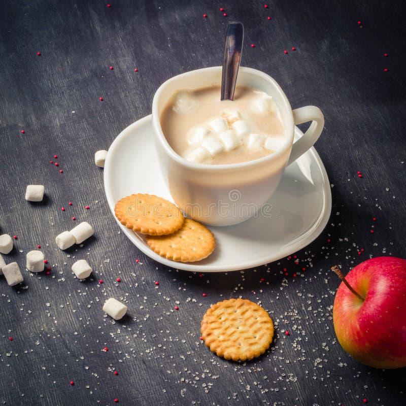 Vit kopp på ett tefat med varm kakao Mörk träbakgrund för morgonfrukost royaltyfria bilder