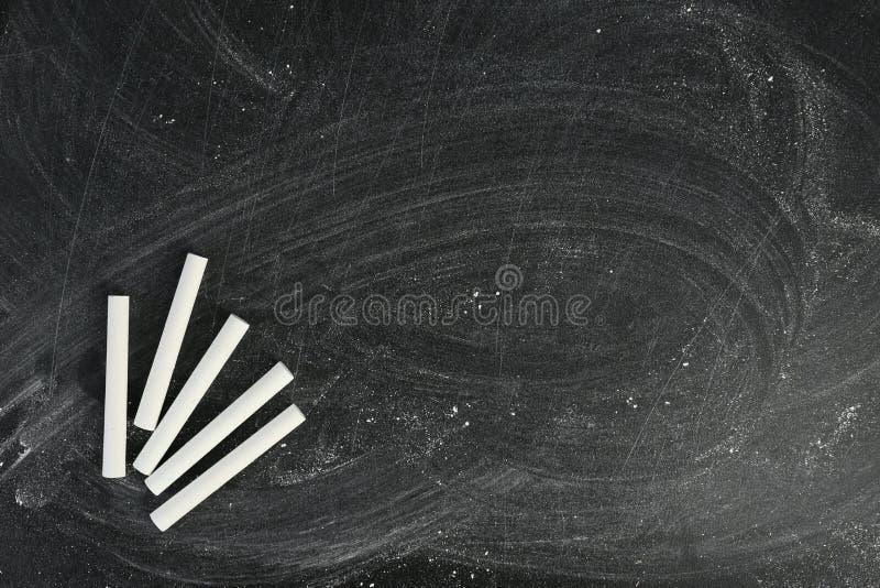 Vit krita på den smutsiga svart tavla med utrymme för text royaltyfria foton