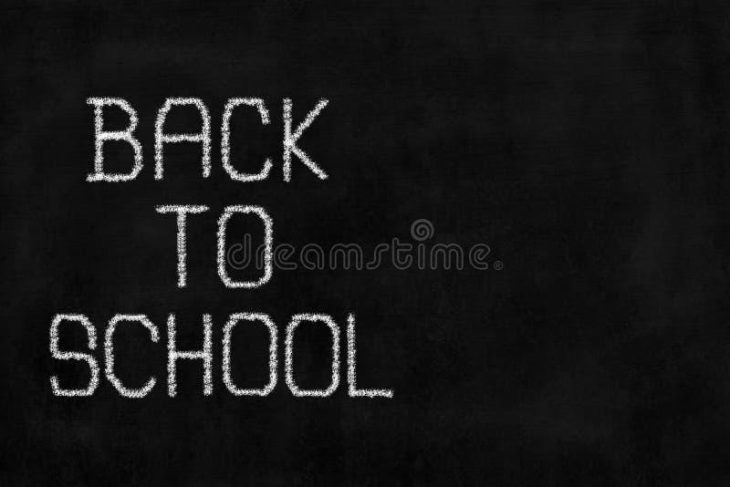 Vit kritahandstil` tillbaka till skola` på den svart tavlan royaltyfri foto