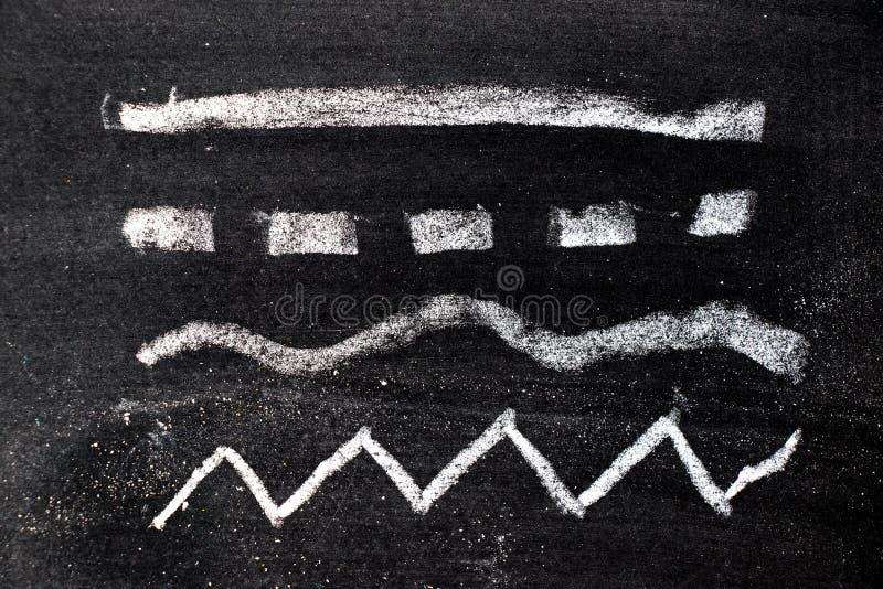 Vit kritahandteckning i uppsättning av linjen form på svart tavlabakgrund royaltyfri fotografi