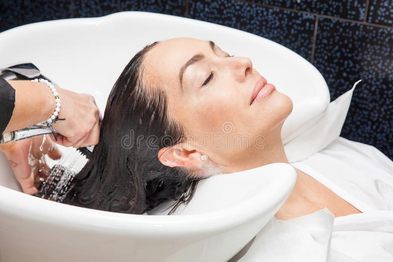Vit kvinna som får en hårwash i en skönhetsalong royaltyfri bild