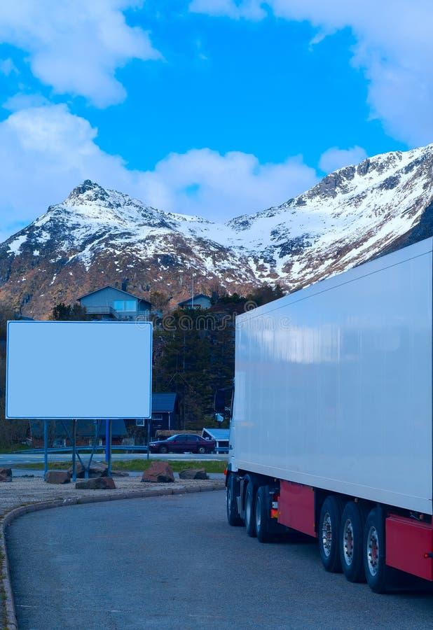Vit kyld lastbil och stor tom affischtavla arkivbilder