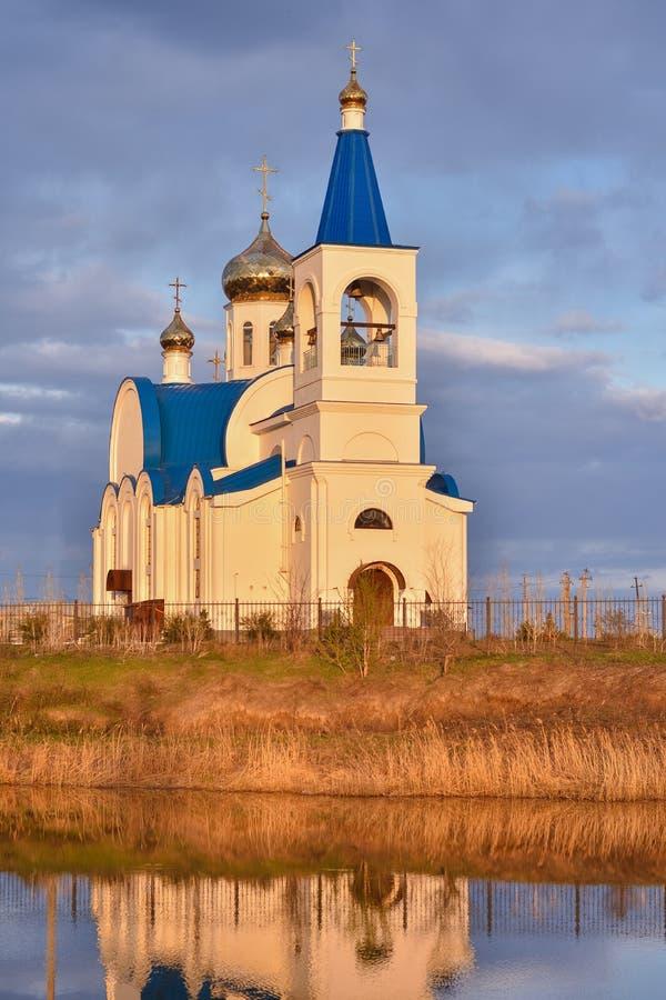 Vit kyrka med det blåa taket på sjön royaltyfria bilder