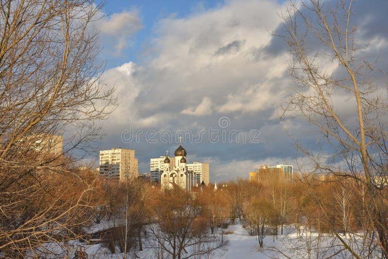 Vit kyrka med svarta kupoler på bakgrunden av bostads- byggnader royaltyfri bild