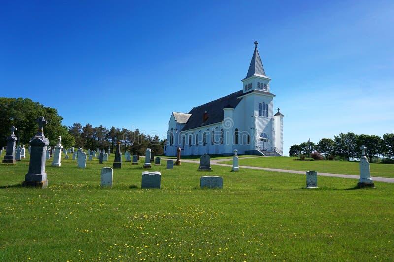 Vit kyrka och kyrkogård under blå himmel royaltyfria bilder