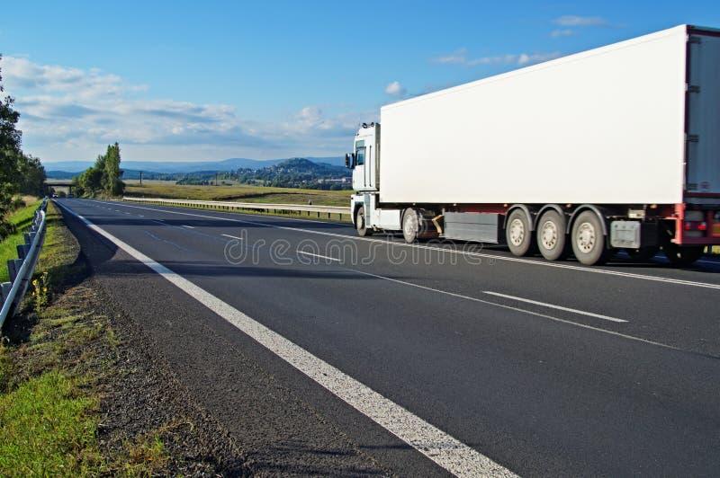 Vit lastbil som kör på vägen ett lantligt landskap arkivfoto