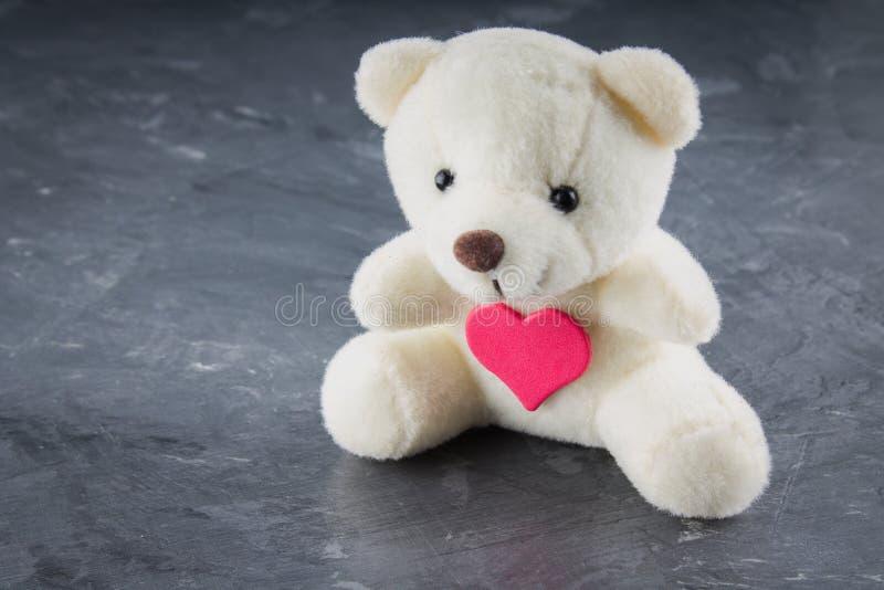 Vit leksaknallebjörn med hjärta på en grå bakgrund Symbolet arkivfoto
