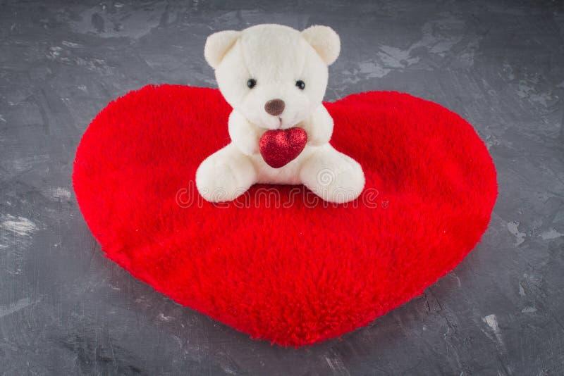Vit leksaknallebjörn med hjärta på en grå bakgrund Symbolet royaltyfria foton