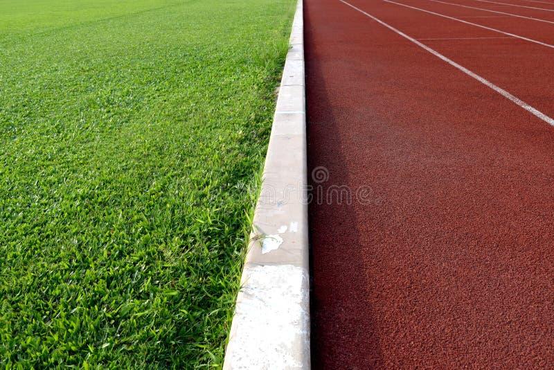 Vit linje mellan fotbollfältet för grönt gräs och spårlandningsbanan arkivbild
