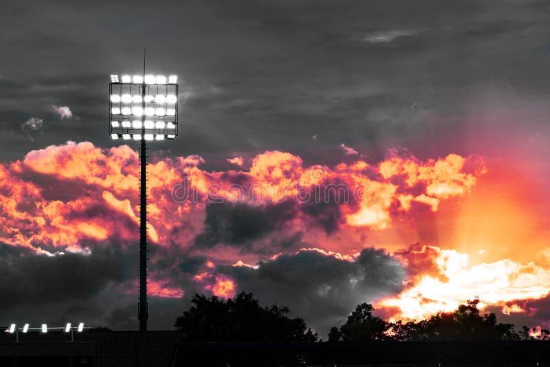 Vit ljus elektrisk pol på sportstadion med dramatiskt himmel och röd orange ljus aftonhimmel royaltyfria foton