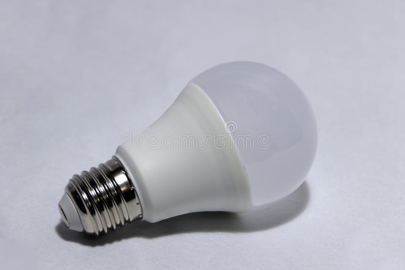 Vit ljus kula på den vita bakgrunden det är en glass kula som sätts in in i en lampa eller en hålighet i tak arkivfoton