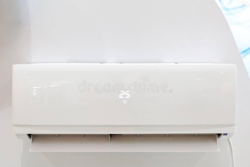 Vit luftkonditioneringsapparat på en vägg med temperaturskärm och en fjärrkontroll Closeupbild royaltyfri fotografi