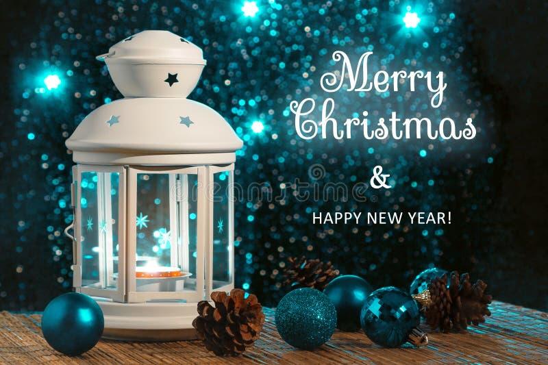 Vit lykta med en brinnande stearinljus och prydnad p? bakgrunden av julgranen med ljus h?rligt arkivbilder