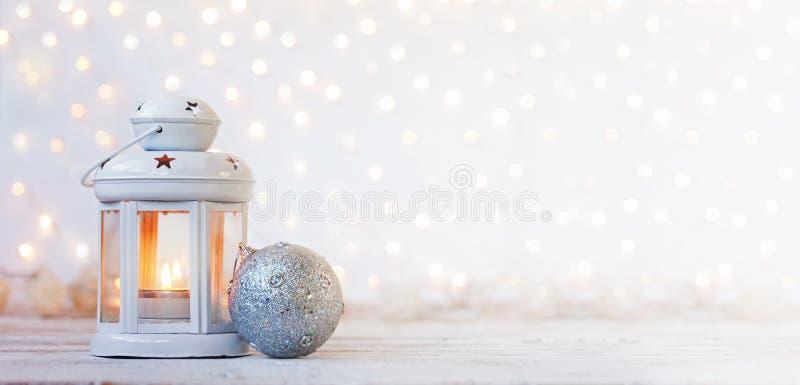 Vit lykta med stearinljus- och silverbollen - julgarnering baner royaltyfri fotografi