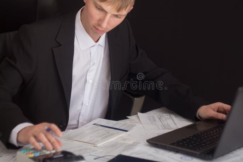 Vit man som arbetar i ett kontor med dokument Chefen gör rapporten och fyller in förklaringen Affärsman på arbete in royaltyfria foton