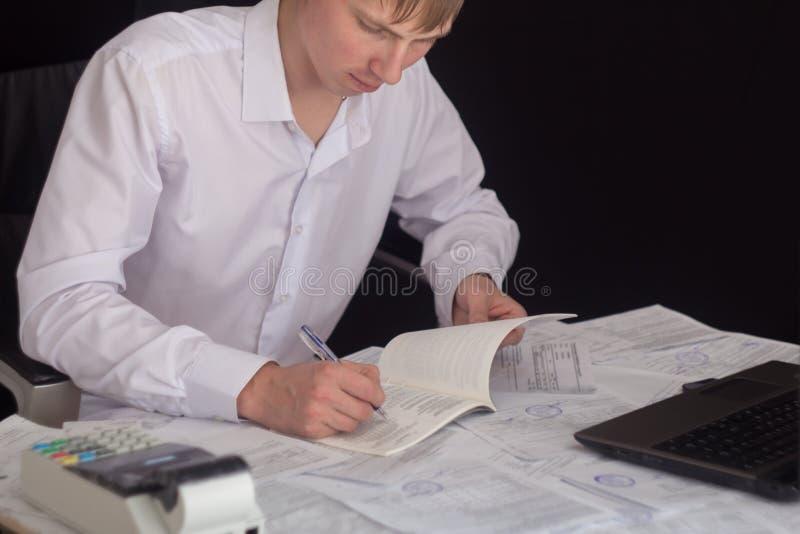 Vit man som arbetar i ett kontor med dokument Chefen g?r rapporten och fyller in f?rklaringen Aff?rsman p? arbete in royaltyfria foton