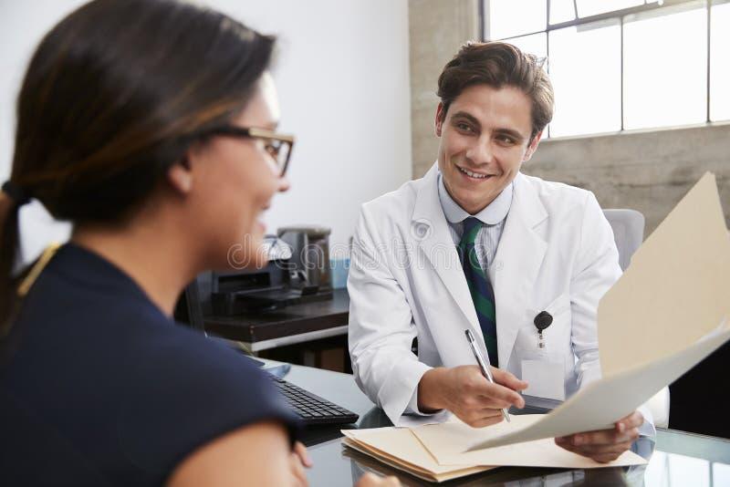 Vit manlig doktorsvisningmapp till den kvinnliga patienten i regeringsställning arkivfoto