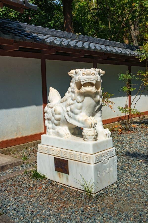 Vit marmorerar den kinesiska lejonstatyn på maingaten av Kamakuraen Daibutsu - stor Buddha av Kamakura arkivfoto