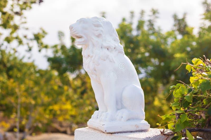 Vit marmorskulptur av ett lejon på sockel arkivfoto