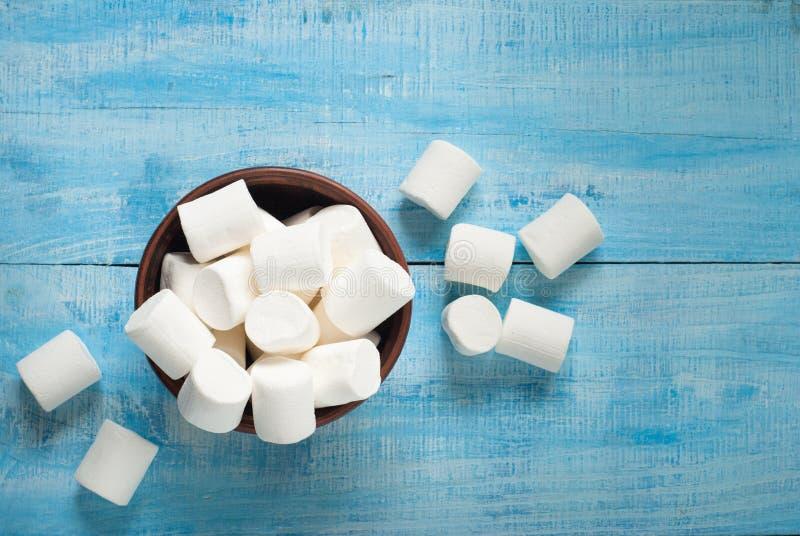 Vit marshmallow i bunke på blått royaltyfri fotografi