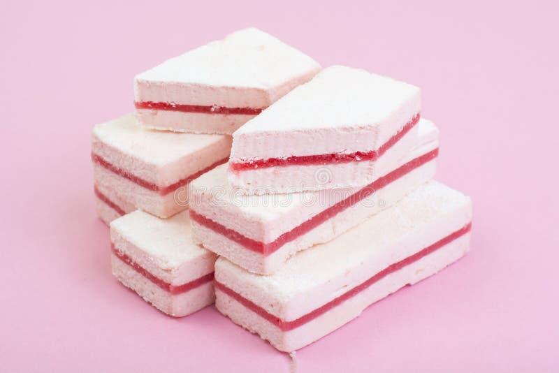 Vit marshmallow med tranbärlagret på pastellfärgad bakgrund arkivfoton