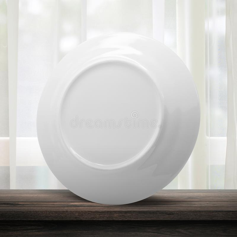 Vit maträtt eller keramisk platta på modern kökbakgrund med tomt dishwarebegrepp Vitt maträttmallställe på trätabellen arkivbild