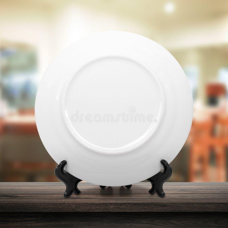 Vit maträtt eller keramisk platta på modern kökbakgrund med tomt dishwarebegrepp Vitt maträttmallställe på trätabellen arkivfoto