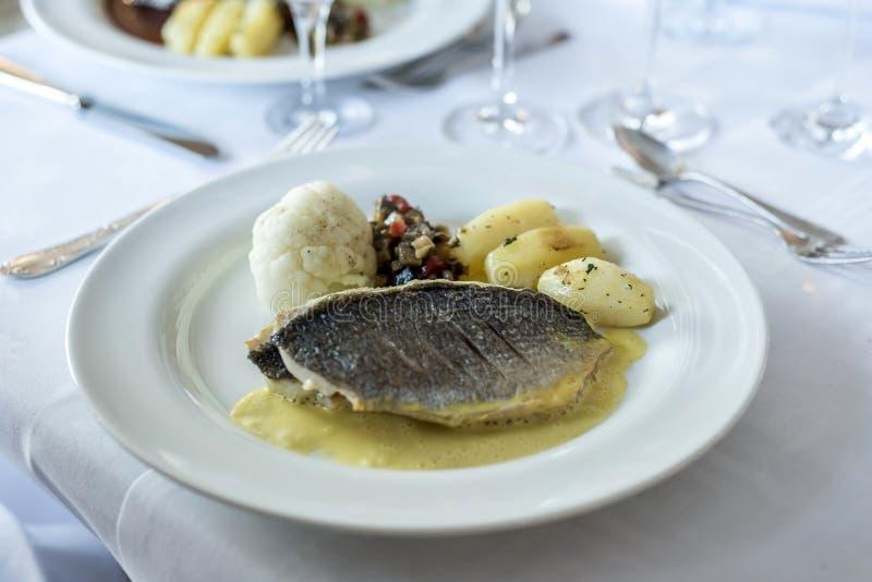Vit matställeplatta med fiskfiletbiff och potatissallad på ett bröllopmål arkivbilder