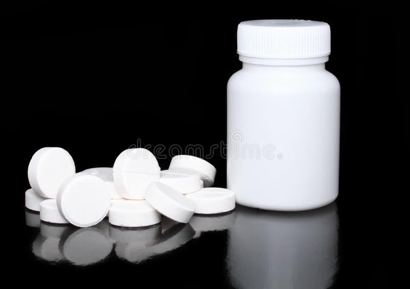 Vit medicinflaska, färgpills på black. royaltyfria bilder