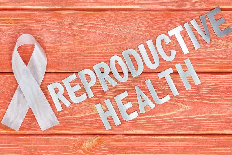 Vit medvetenhetband och inskrift av järnbokstäver: reproduktiv hälsa som ligger på trätexturerad bakgrundsfärg av säsongen fotografering för bildbyråer