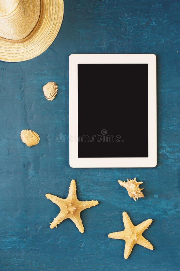 Vit minnestavla med den tomma skärmen, sugrörhatten, skal och sjöstjärnan royaltyfri bild