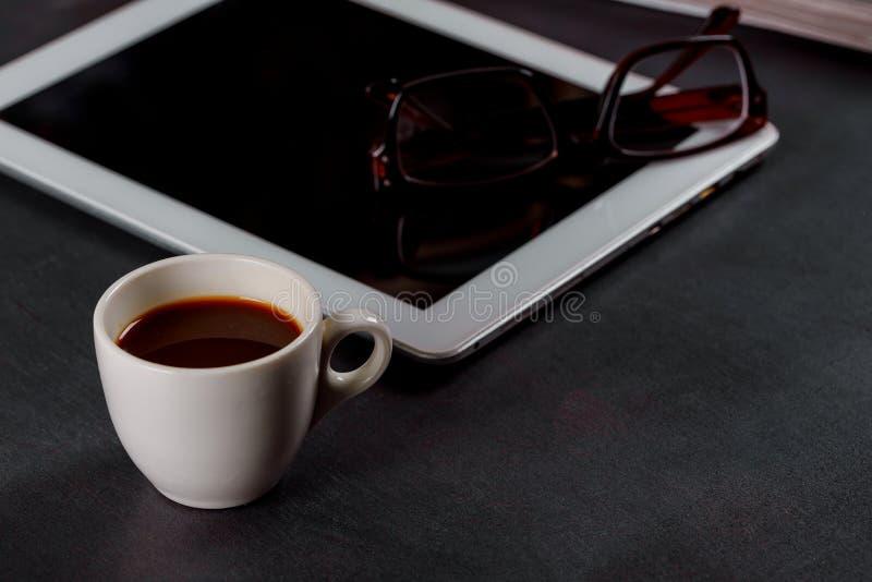 Vit minnestavladator på en trätabell med exponeringsglas, en kopp av svart kaffe arkivbild