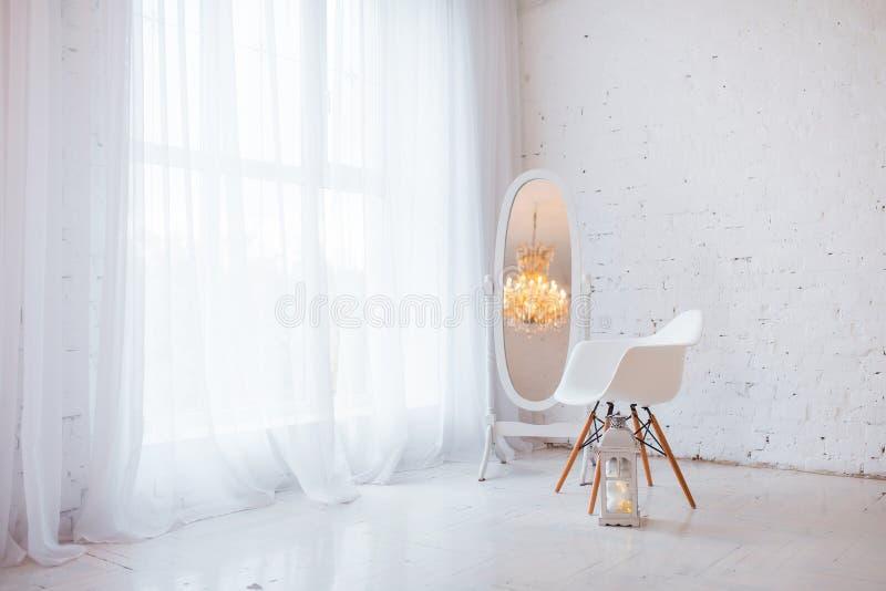 Vit modern stol i inre rum för vind med det stora fönstret och spegeln royaltyfri fotografi