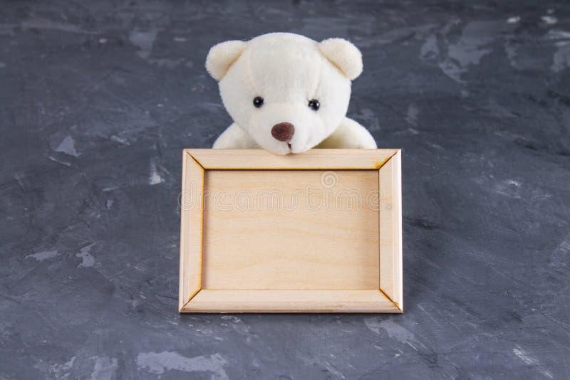 Vit nallebjörn som rymmer den tomma träramen Grå färgbakgrund arkivbild