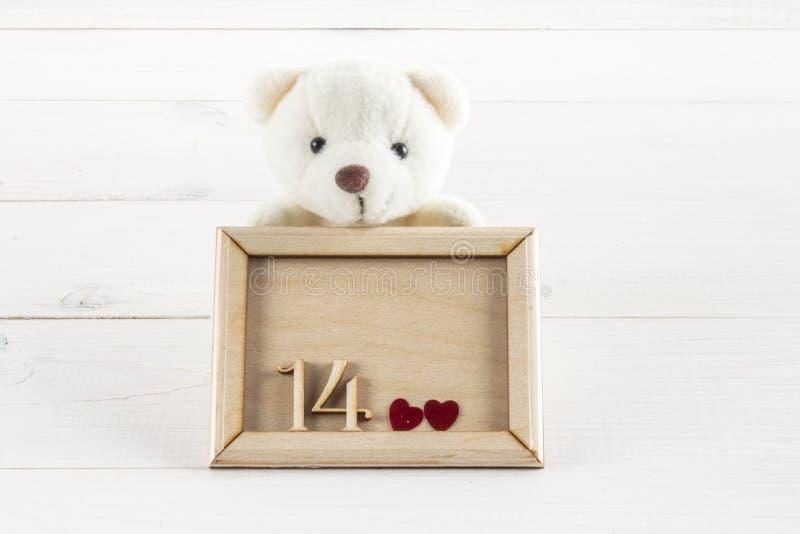 Vit nallebjörn som rymmer plattan med hjärtor Begrepp på 14 Februari royaltyfri bild