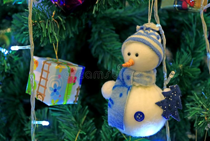 Vit och blå snögubbeprydnad med den fyrkant formade gåvaasken som hänger på den mousserande julgranen arkivbild