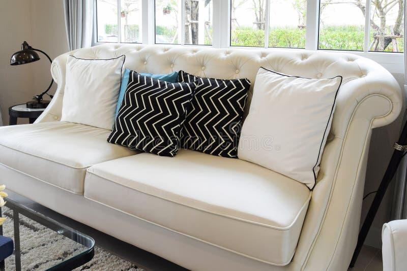 Vit- och blåttkuddar på ett vitt läder uttrycker i vardagsrum royaltyfri bild