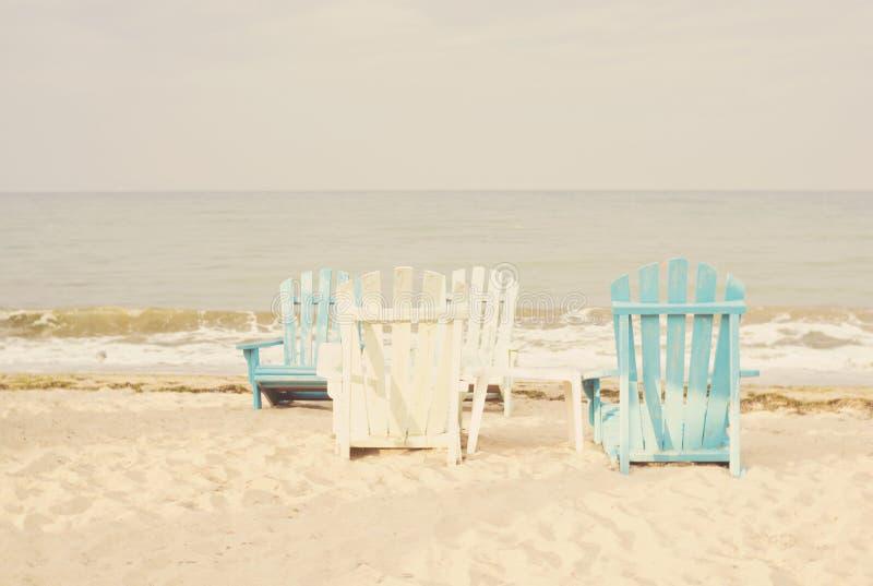 Vit- och blåttstrandstolar på sandseascape och ljus himmel i sommarsemester kopplar av Tappningfilter som tonar, sologenomskinlig royaltyfria foton