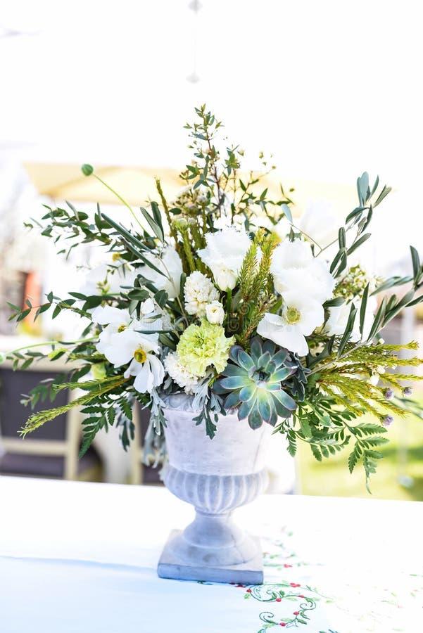Vit- och gräsplanvariation av blommor i en stor central tabellbukett arkivfoto