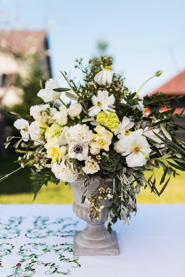 Vit- och gräsplanvariation av blommor i en stor central tabellbukett fotografering för bildbyråer