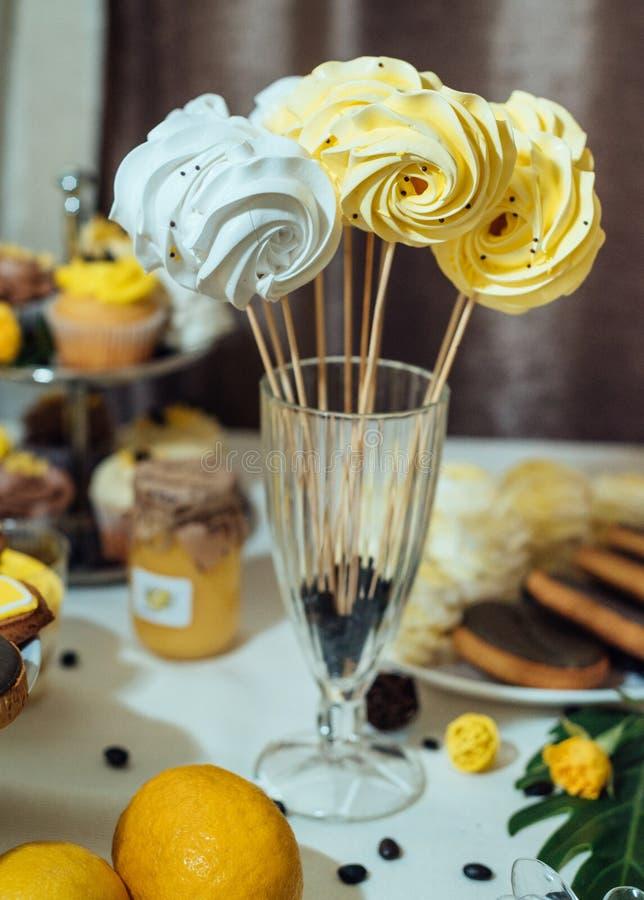 Vit- och gulingmarängar på pinnen i exponeringsglas med kaffebönor Semestra godisstången i guling- och bruntfärg Bröllopgodisstån arkivbilder