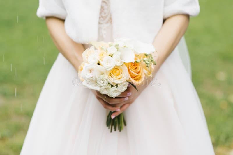 Vit och orange gifta sig bukett i händerna fotografering för bildbyråer