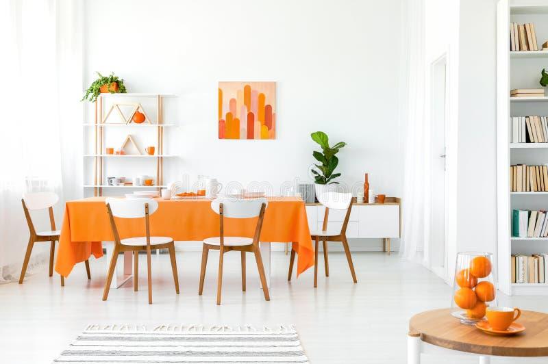Vit och orange matsal med målning på väggen, bokhyllan i hörnet och den gröna växten royaltyfria bilder