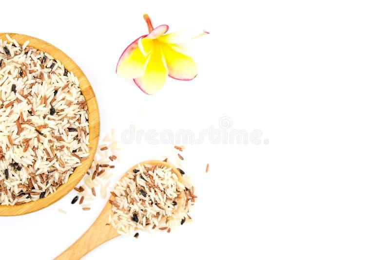Vit och råriers för bästa sikt blandad i en träbunke och en träsked, färgrikt riskorn som isoleras på vit bakgrund royaltyfri foto